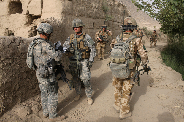 Paratroopers from the 3rd Battalion Parachute Regiment, soldiers from the U.S.-led Task Force Paladin and an unidentified U.S citizen from Dallas, Texas, center, working as a civilian contractor to advise the U.S.-led Task Force Paladin, take part in an operation to search three compounds and look for weapons in Salavat, Panjawi Province, Afghanistan.