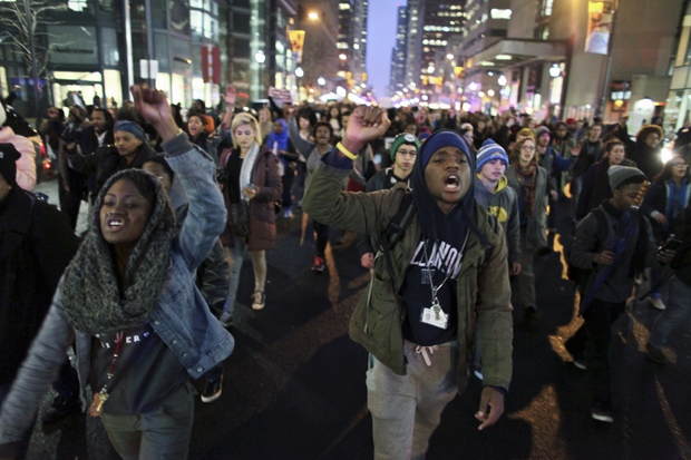 People march along Market Street as they participate in a demonstration, Wednesday Dec. 3, 2014, in Philadelphia.  The crowd, protesting the deaths of two unarmed black men at the hands of police,  rallied at the train station and marched through downtown before disrupting a tree lighting ceremony at City Hall.