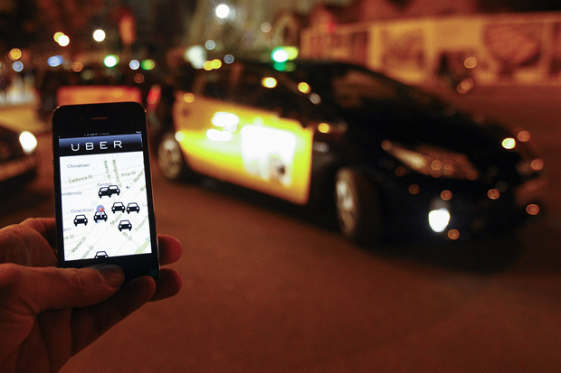 The Uber app is seen on a smartphone past cabs waiting for clients near the Sagrada Familia in Barcelona, on December 9, 2014. A judge on December 9, 2014 banned the popular smartphone taxi service Uber from operating in Spain, court officials said, following similar prohibition action in several other countries.