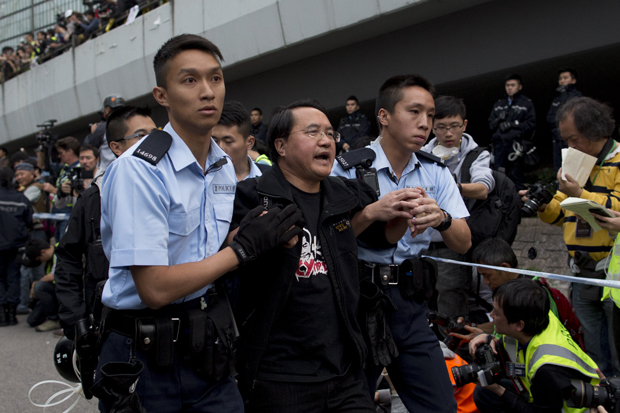 Police officers arrest a pro-democracy protester outside Hong Kong's Government complex on December 11, 2014. After more than two months and drawing crowds of over 100,000, the main Admiralty pro-democracy protest site is being cleared away by bailiffs and police after a court injunction paved the way for officials to clear three parts of the site.