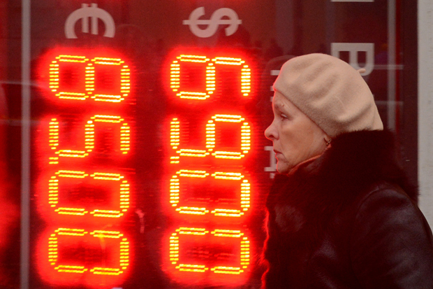 A woman walks past a board listing foreign currency rates against the Russian ruble outside an exchange office in central Moscow on December 16, 2014. The Russian ruble set a new all-time record low on Tuesday after bouncing back briefly despite an emergency move by Russia's central bank to raise interest rates to 17 percent.