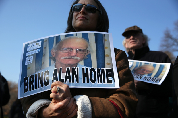 This 2013 photo shows supporters holding signs to call on the U.S. to bring home U.S. citizen Alan Gross, who was held in a prison in Cuba.  Gross was released Dec. 17.