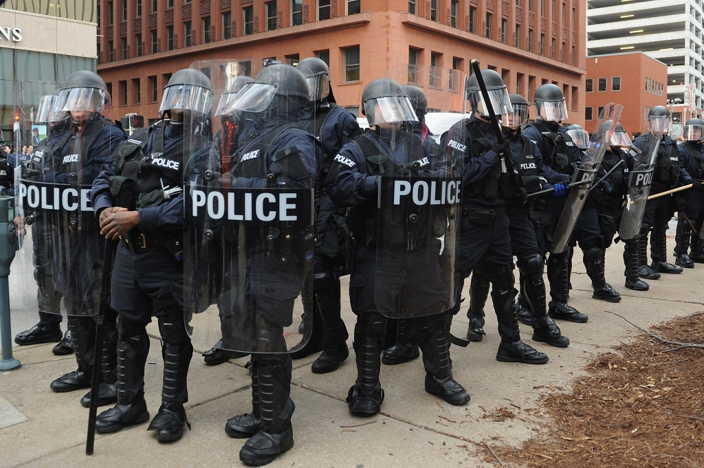 Police officers stand on alert after an arrest was made during a protest in downtown St. Louis, Missouri on November 30, 2014. Demonstrators marched through the streets of St. Louis that eventually led to clashes with police officers and fans from an American Football game between the St. Louis Rams and Oakland Raiders.