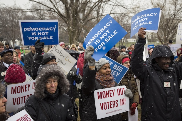 Attendees hold signs and cheer Jan. 21 during a rally calling for an end to corporate money in politics and to mark the fifth anniversary of the Supreme Court's Citizens United decision at Lafayette Square, near the White House in Washington, D.C.