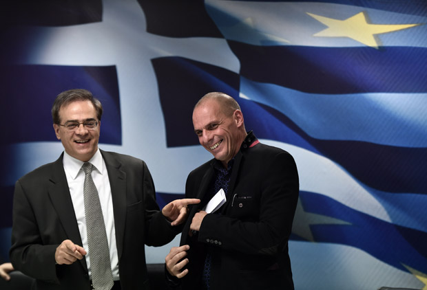 Greece's outgoing Finance minister Gikas Hardouvelis (L) jokes with the new Finance minister Yanis Varoufakis after a ministry hand-over ceremony Jan. 28 in Athens.