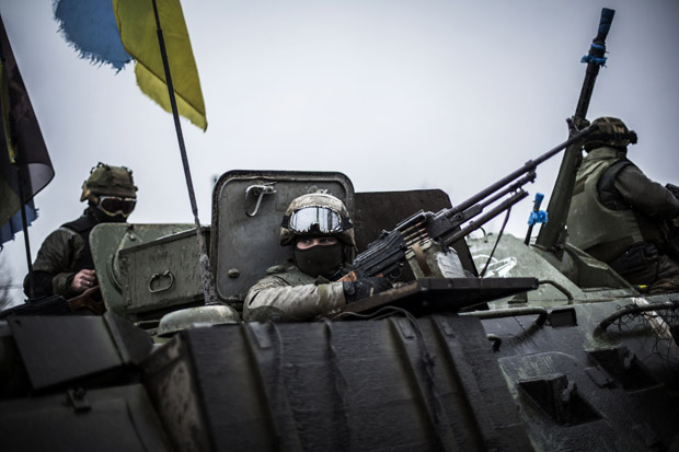 Ukrainian soldiers are seen in an armored vehicle topped with a Ukrainian flag near the city of Artemivsk, in the Donetsk region, before heading to the city of Debaltseve about 45 km away, on February 1, 2015. Civilians fleeing the besieged east Ukrainian town of Debaltseve came under withering artillery fire from pro-Russian separatists on February 1, with security forces vowing to fight to the end to defend the key transport hub.