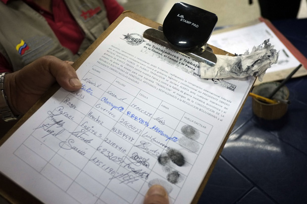 People sign documents March 9 to show their support for the Venezuelan government after the United States imposed sanctions on Venezuelan officials over rights abuses.