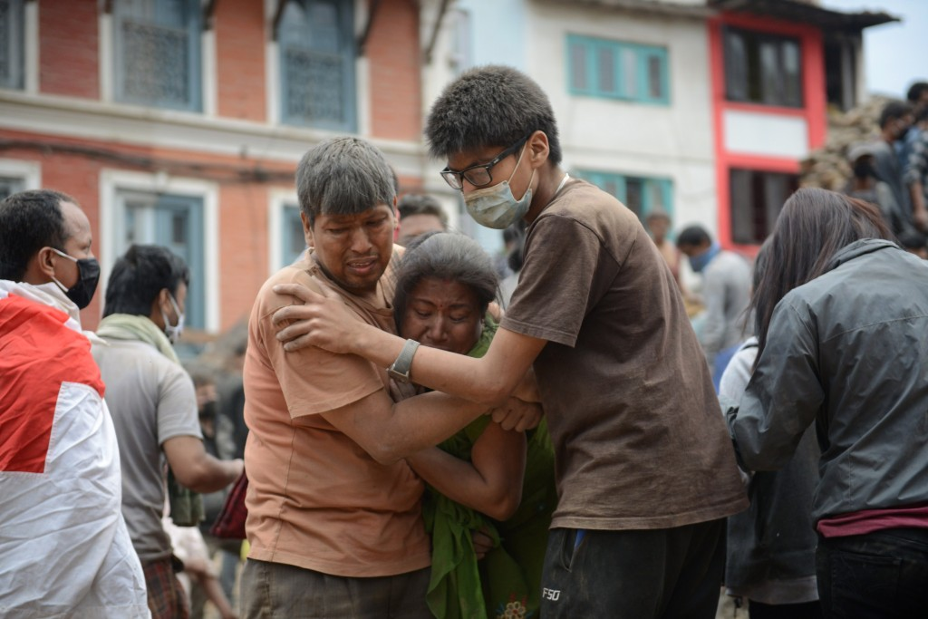 Earthquake victims are helped by a rescuer in Kathmandu's Durbar Square after an earthquake on April 25, 2015.
