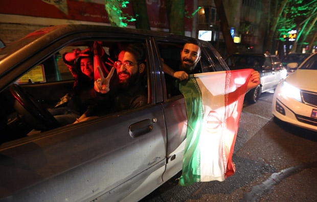 """People flash the """"V for Victory"""" sign and hold an Iranian flag out of a car window April 2 as they celebrate on Valiasr street in northern Tehran after the announcement of an agreement on Iran nuclear talks."""