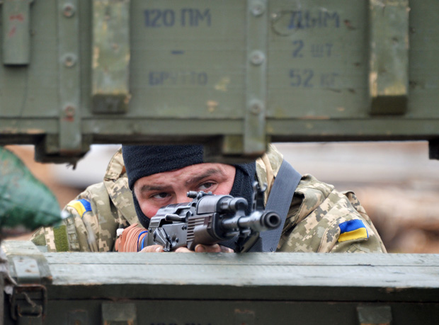 An Ukrainian serviceman mans position April 14 in Berdyanske village, west of where the use of heavy weapons has been reported on the outskirts of the strategic port city of Mariupol.