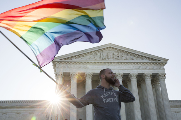 Same-sex marriage supporter Vin Testa, of Washington, DC, waves a rainbow pride flag  April 28, 2015 near the Supreme Court in Washington, D.C.