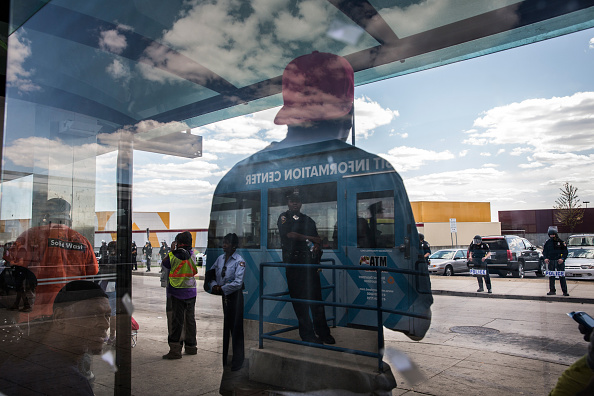 People wait for the bus at the Mondawmin Station while police secure Mondawmin Mall on April 29, 2015 in Baltimore, Maryland.