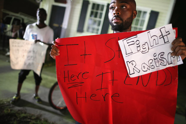Curtis Clayton holds a sign protesting racism in the wake of the shooting at the historic Emanuel African Methodist Episcopal Church  in Charleston, South Carolina.