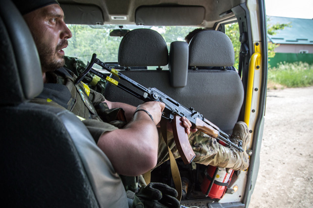 A Ukrainian serviceman holds a weapon as he sits in a car June 4 during fightings in the Ukrainian city of Mariinka.