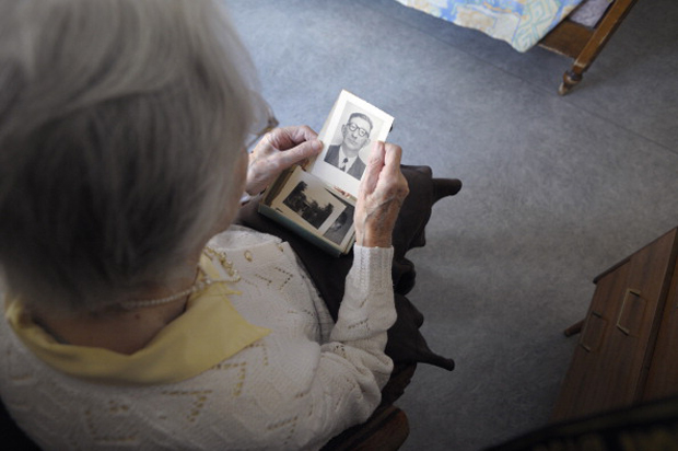 A woman, suffering from Alzheimer's disease looks at an old picture in a retirement house in Angervilliers, eastern France.