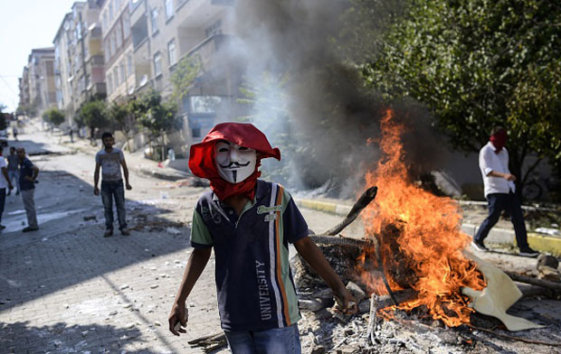 "A left-wing militant wearing a ""Guy Fawkes"" mask stands by a burning barricade July 26 during clashes with Turkish riot police in Istanbul's Gazi district."