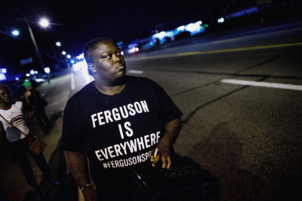 Demonstrators, marking the one-year anniversary of the shooting of Michael Brown, protest Aug. 11 along West Florrisant Street in Ferguson, Missouri.