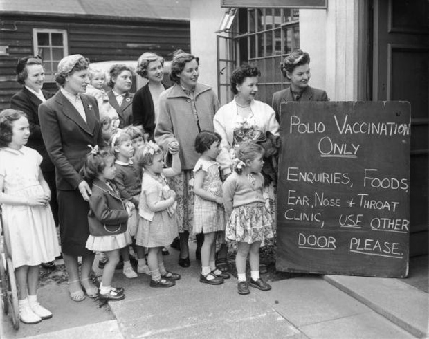 This 1956 photo shows a group of mothers with their children outside the Middlesex County Council Clinic, waiting for the first polio vaccinations to begin.