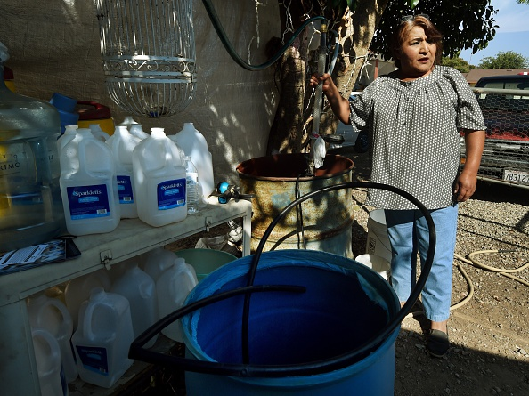 Maria Jimenez demonstrates how they pump bottled water up to a storage tank on the roof of their rented house to wash in the drought affected town of Monson, California.