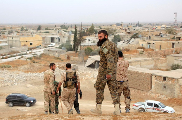 Syrian government forces walk in the village of Jabboul on the eastern outskirts of the northern Syrian city of Aleppo after taking control of the village from Islamic State militants on Oct. 24.