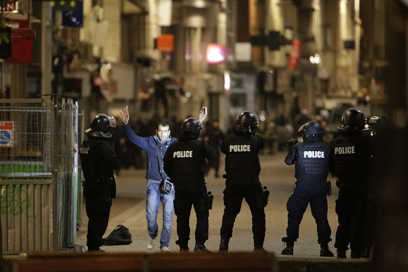 A passerby raises his arms in front of Police forces on Wednesday in the northern Paris suburb of Saint-Denis as police special forces raid an appartment, hunting those behind the attacks that claimed 129 lives in the French capital five days ago.