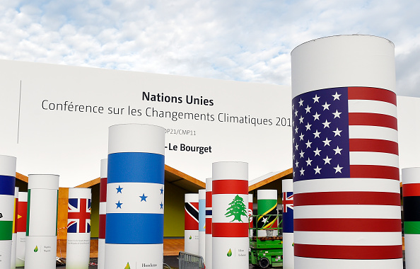 Pillars with the names and national flags of countries attending the UN climate conference known as COP 21 decorate the outside of the venue hall in Le Bourget, north of Paris.