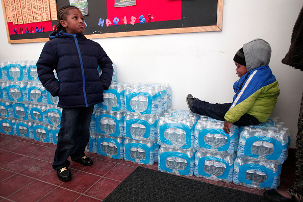 Justin Roberson, left, age 6, and Mychal Adams, age 1, of Flint, Michigan, wait on a stack of bottled water at a Jan. 17 rally where the Rev. Jesse Jackson was speaking about the city's water crisis.