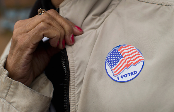 "A voter shows off her ""I Voted"" sticker as she leaves a polling place on Nov. 4, 2014, in Ferguson, Missouri."