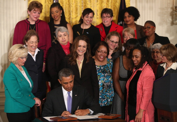 President Barack Obama signs an executive order in April 2014 intended to force federal contractors to address unequal pay. He presented new rules last week that would require companies with 100 or more employees to include salary information on a form they already submit that reports employees' sex, age and job groups.