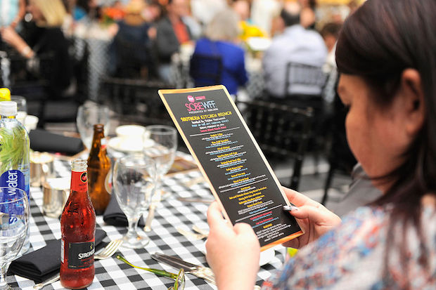 A guest views a menu at the Southern Kitchen Brunch Hosted By Trisha Yearwood — part of The New York Times Cooking Series — at Loews Miami Beach Hotel on February 28, 2016 in Miami Beach, Florida.