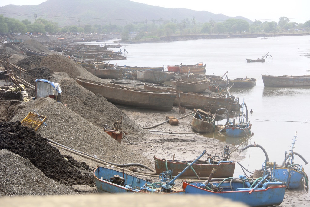 Sand miners' boats and suction pumps in India.