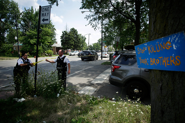 Chicago Police officers hang yellow crime scene tape where a man was shot multiple times as he sat in a vehicle July 27 in Chicago, Illinois.