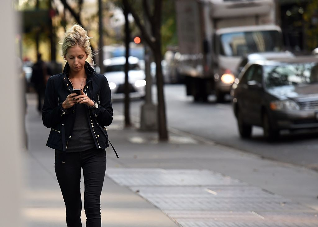 A woman uses her smart phone as she walks on 47th Street November 13, 2014 in New York.   AFP PHOTO/Don Emmert        (Photo credit should read DON EMMERT/AFP/Getty Images)