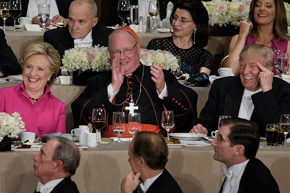 From left Democratic presidential nominee Hillary Clinton, Timothy Cardinal Dolan, Archbishop of New York, and Republican presidential nominee Donald Trump laugh during the Alfred E. Smith Memorial Foundation Dinner at Waldorf Astoria October 20, 2016 in New York, New York.