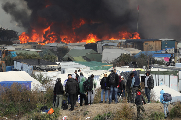 Fire breaks out in the Jungle camp as migrants prepare to leave while the authorities start to demolish the site on October 26, 2016 in Calais, France.