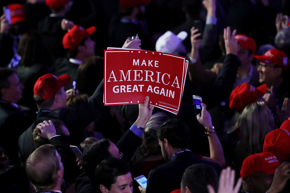 "An attendee of Donald Trump's victory rally in New York City holds up a sign  that reads ""Make America Great Again."""
