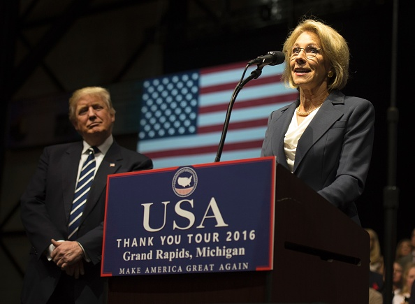 US President-elect Donald Trump listens as Betsy DeVos, his pick for education secretary, speaks during the USA Thank You Tour December 9, 2016 in Grand Rapids, Michigan.