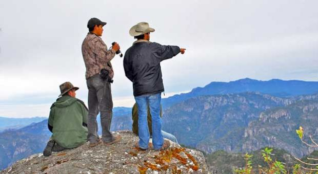 From left to right, Martjan Lammertink, Manuel Escarcega, and Tepehuan guide Rafael look across the vast chasm of Taxicaringa Canyon. The paramilitary drug cartel Los Zetas controls the area on the other side.