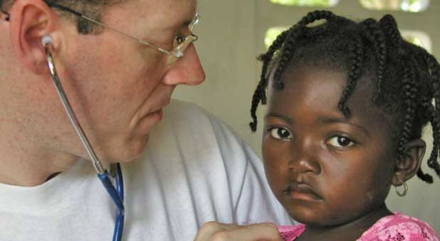 Dr. Paul Farmer, co-founder of Partners In Health, an organization that builds hospitals and provides heathcare to countries afflicted by poor health conditions, attends to one of his patients in rural Haiti.
