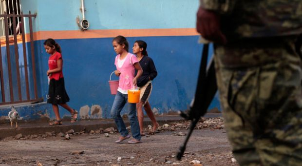 Girls are escorted by soldiers as they walk in Huatla village, Heliodoro Castillo municipality, Guerrero State, Mexico, on August 3, 2013. Huatla is one of 13 villages from where residents have left due to murders, threats and kidnappings by drug cartel members.
