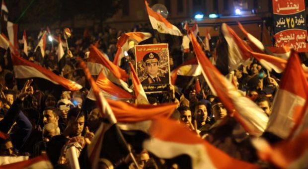 Egyptians wave the national flag and hold up pictures of Defense Minister army chief Abdel Fattah al-Sisi during a gathering in General Abdel Monim Riyad square at the edges of Cairo's Tahrir square on January 25, 2014. A spate of deadly bombings put Egyptian police on edge as supporters and opponents of the military-installed government take part in rival rallies for the anniversary of the 2011 Arab Spring uprising.