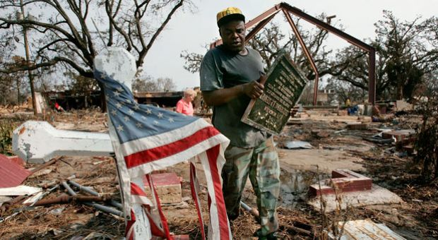 Thomas Walker, the sexton of the Episcopal Church of the Redeemer, carries a bronze plaque from the church which was destroyed by Hurricane Katrina as he walks with lifetime church member Melba Smith September 1, 2005 in Biloxi, Mississippi. Biloxi was devastated by Hurricane Katrina and hundreds are feared dead along the Mississippi coastline.
