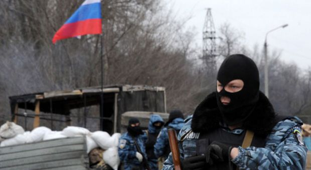 Armed masked men who call themselves members of Ukraine's disbanded elite Berkut riot police force stand at their checkpoint under a Russian flag on a highway that connect Black Sea Crimea peninsula to mainland Ukraine near the city of Armyansk, on February 28, 2014. The spiralling tensions in a nation torn between the West and Russia today took a severe new turn when Ukraine's interim president Oleksandr Turchynov accused Russian soldiers and local pro-Kremlin militia of staging raids on Crimea's main airport and another base on the southwest of the peninsula where pro-Moscow sentiments run high.