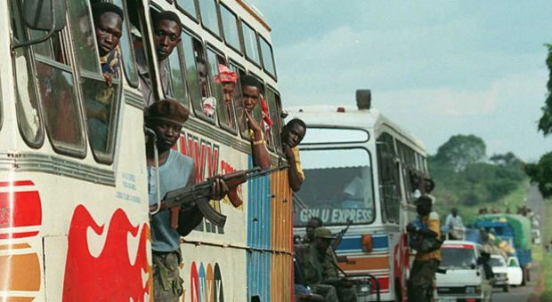 Ugandan soldiers accompany a convey of buses and private cars into the northern Ugandan town of Gulu on March 21, 1996, after Ugandan Lord's Resistance Army (LRA) rebels attacked three villages in the northern part of the country March 18 and 19, killing 34 people.