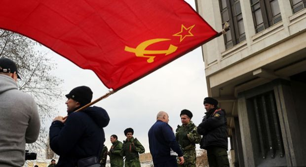 A man holds a Soviet-era flag as dozens of Russian Cossacks surround the parliament building in a show of support for Russia on March 6, 2014 in Simferopol, Ukraine. Dozens of Russian Cossacks surrounded the building in a show of support for Russia. As the standoff between the Russian military and Ukrainian forces continues in Ukraine's Crimean peninsula, world leaders are pushing for a diplomatic solution to the escalating situation. Crimean citizens will vote in a referendum on 16 March on whether to become part of the Russian federation.