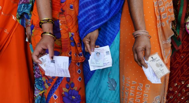 Indian voters pose with their voting slips as they stand in a line to cast their vote outside a polling station at Dabua village on the outskirts of Faridabad on April 10, 2014, during the third stage of voting for national elections in the northern state of Haryana. India's upstart anti-graft party faced a key test as the national capital voted in the first major phase of the country's marathon general elections. The third phase of voting began at 7 a.m.  in 91 constituencies, representing nearly a fifth of the 543-seat lower house, across the capital and 13 other states, including Maoist insurgency-hit eastern India.