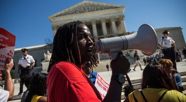 Tabrian Joe, a Sophomore at Western Michigan University, leads a protest in support of affirmative action, outside the Supreme Court during the hearing of 'Schuette v. Coalition to Defend Affirmative Action' on October 15, 2013 in Washington, DC. The case revolves around affirmative action and whether or not states have the right to ban schools from using race as a consideration in school admissions.  The Supreme Court upheld Michigan's ban on affirmative action on April 22, 2014.