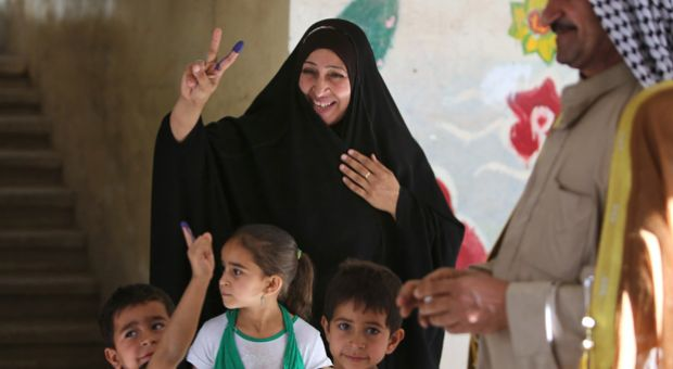 Caption: An Iraqi woman and her children display ink-stained fingers after she cast her ballot in Baghdad's Sadr City district during her country's general elections on April 30, 2014. Iraqis streamed to voting centers nationwide, amid the worst bloodshed in years, as Prime Minister Nuri al-Maliki seeks reelection.