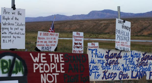 Protesters hang signs on a fence along US. highway 170 protesting the closure of thousands of acres of Bureau of Land Management land that has been temporarily closed to round-up illegal cattle that are grazing south of Mesquite Nevada on April 10, 2014 in Mesquite, Nevada. BLM officials are rounding up ranchers Cliven Bundy's cattle, who has been locked in a dispute with the BLM for a couple of decades over grazing rights.
