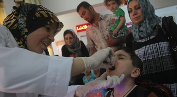 An Iraqi doctor gives a polio vaccine to a child at a health clinic in Baghdad. Iraq aims to vaccinate millions of children across the country against the highly contagious polio virus in response to an outbreak of the disease in the country as well as the region.